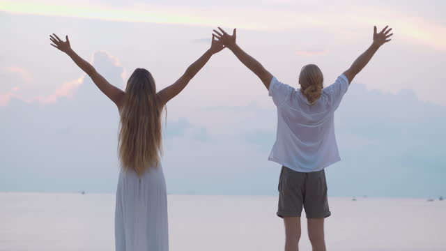 rear view,happy of couple age 25-29 yearold of latin american and hispanic ethnicity raises arms into air while open arms enjoying travel holidays beautiful beach sea on sunset together.open arms concept. - wonderlust stock videos & royalty-free footage