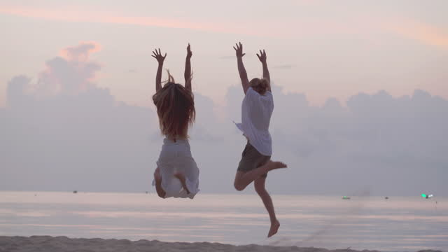 rear view,happy of couple age 25-29 yearold of latin american and hispanic ethnicity holding hand while run and jumping enjoying travel holidays beautiful beach sea on sunset together.happiness in nature concept. - discovery stock videos & royalty-free footage