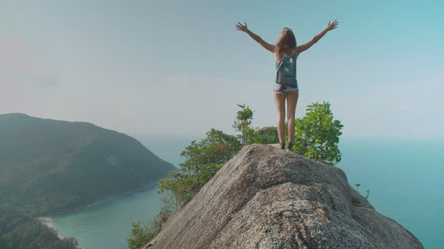 rear view,happy of freedom travelers women age 29 yearold of atin american and hispanic ethnicity raises arms into air while open arms enjoying travel holidays on top of mountain ocean summit.open arms concept. - wonderlust stock videos & royalty-free footage