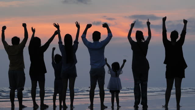 rear view,in silhouette happy to multi generation family of eight people raises arms into air while looking at view and open arms enjoying travel holidays on the beach at sunset.open arms concept. - wonderlust stock videos & royalty-free footage