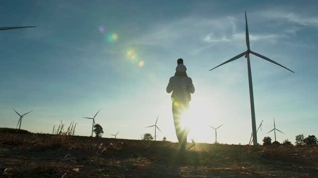 rear view,in silhouette sunset of family,baby boy age 17 month ride the neck of father while look and walking between the wind turbines with great freedom.teaching children about sustainability concept. - hope stock videos & royalty-free footage