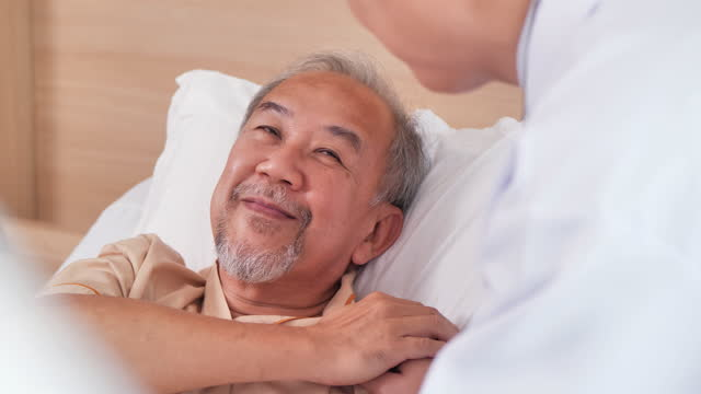 rear view,male nurse doctor visits to asian senior men age 60 yearold lying on the bed talking and consoling while touch of shoulder him at hospital. healthcare worker giving support and solution to patient together.senior care concept. - trust stock videos & royalty-free footage