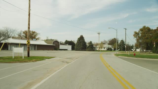 rear window driving pov down main street in a small americana town. - targa con nome della via video stock e b–roll