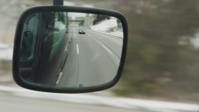 rearview mirror of a commercial bus driving down an interstate during winter, a car approaches in the next lane. - buss bildbanksvideor och videomaterial från bakom kulisserna