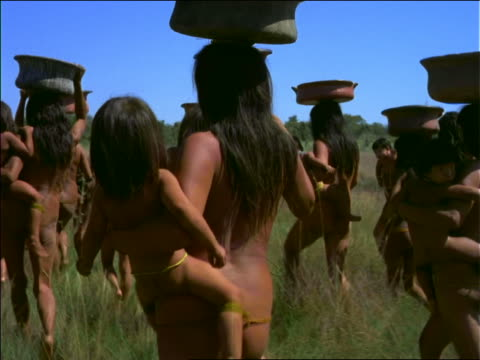 stockvideo's en b-roll-footage met rearview nude native women with baskets on head carrying babies / amazonas, brazil - latijns amerikaanse cultuur