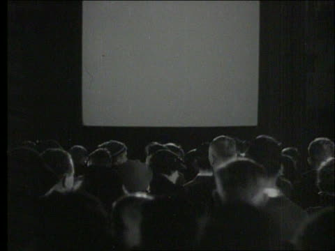 b/w rearview of audience sitting in movie theatre / screen is blank - projektionswand stock-videos und b-roll-filmmaterial