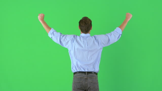 Rearview of businessman raising his arms in excitement on greenscreen