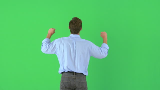 vídeos de stock e filmes b-roll de rearview of businessman raising his arms in excitement on greenscreen - braço humano