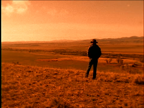 vidéos et rushes de rearview of cowboy looking over plains / zoom in / wyoming - grandes plaines américaines