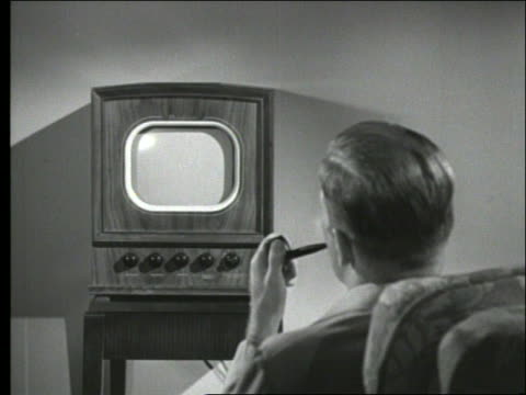 B/W rearview of man smoking pipe watching television / 1950's
