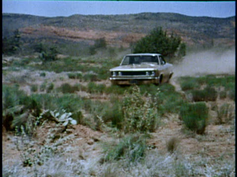 montage ws amc rebel driving through desert and toward camera/ ms rebel driving over hill and away from camera/ usa - in der luft schwebend stock-videos und b-roll-filmmaterial