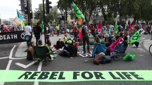 'rebel for life' banner displayed amid masked protestors with flags during a climate change protest organized by extinction rebellion near parliament... - road signal stock videos & royalty-free footage