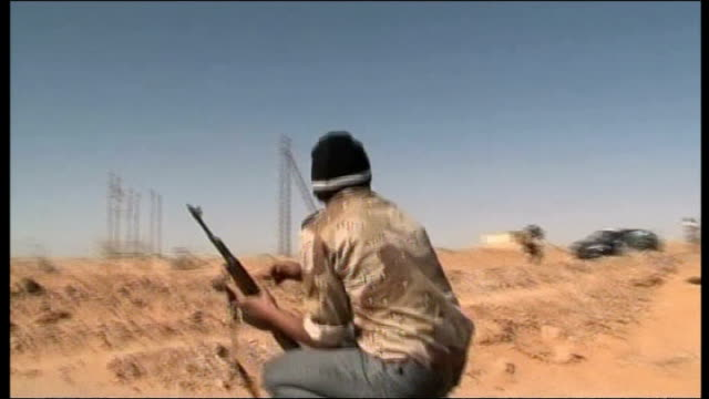 vidéos et rushes de british sbs forces freed by rebels / hague criticised in commons 6311 libya nr benghazi round rebel fighter squatting in desert area as shooting from... - anti aérien