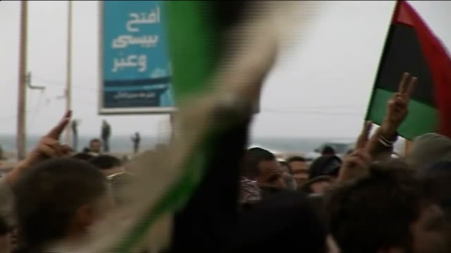 Coalition planes may have killed several civilians LIBYA Benghazi EXT AntiGaddafi protesters march along street waving coalition forces flags and...