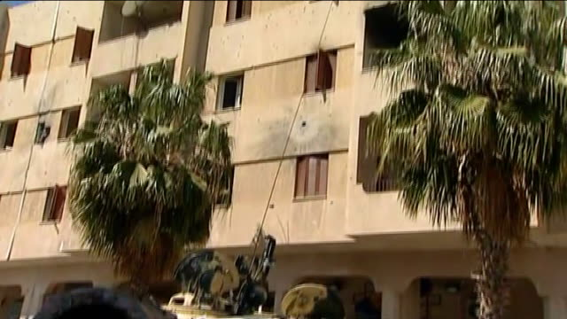 government troops and rebels fight for control of zawiyah reporter along street with rebels bullet holes in wall of building vox pop as explosion... - az zawiyah stock videos & royalty-free footage