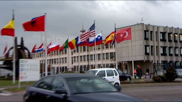 International reaction BELGIUM Brussels EXT Flags on flagpoles PULL OUT vehicles arriving for NATO meeting Ministers seen inside building