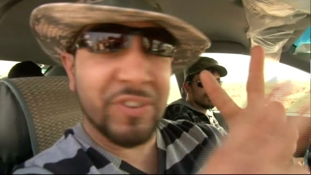 Rebels advance towards Gaddafi stronghold of Sirte Libyan rebel fighters and trucks with black smoke billowing on horizon Reporter to camera Vox pop...