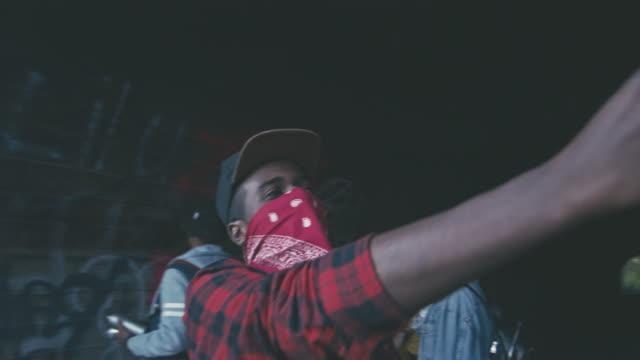 Rebellious African man win bandana covering face recording himself