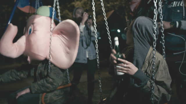 Rebellious Asian woman riding swings and hanging out with friends at night