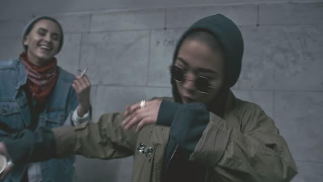 Rebellious group of people smoking and dancing inside underground walkway
