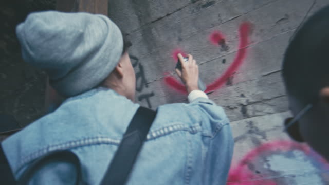 rebellious young people drawing graffiti - graffiti stock videos & royalty-free footage