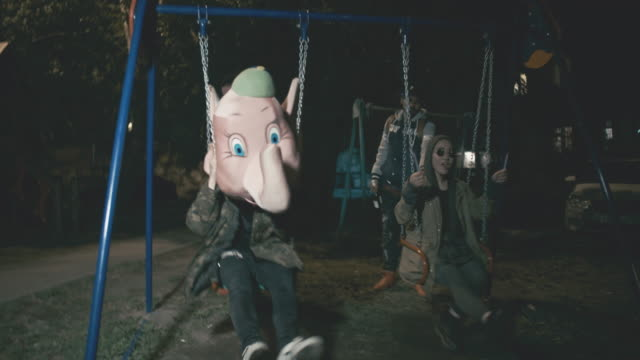 rebellious young people riding swings at night - 無秩序点の映像素材/bロール