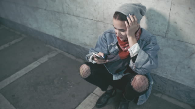 rebellious young woman using mobile phone while sitting inside subway station - fishnet stock videos and b-roll footage