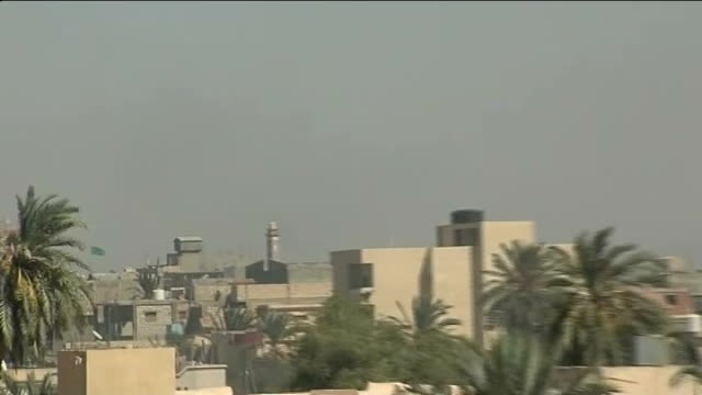 rebels claim to have taken oil refinery in zawiya ext zawiya city skyline zoom in colonel gaddafi green flag flying over gate to town - az zawiyah stock videos & royalty-free footage