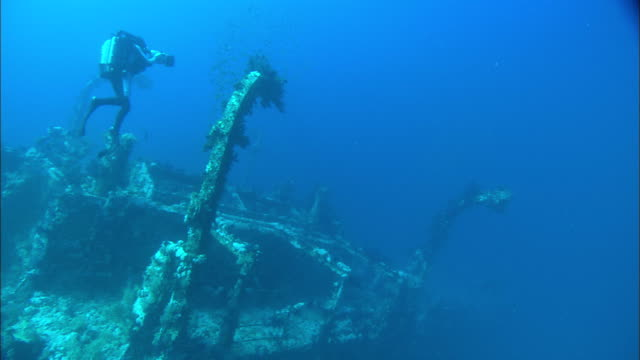 rebreather diver filming wreck dive, hovering above cabin, framed by davits, egypt, red sea  - shipwreck stock videos and b-roll footage