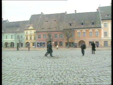 sibiu seq woman wails sof as body of relative laid in coffin gv town square as people to and fro zoom in window in roof of building at far side ls... - atrium grundstück stock-videos und b-roll-filmmaterial