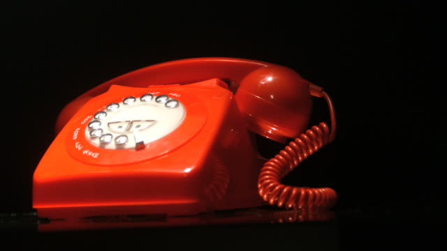receiver falling onto red dial phone on black background - rotary phone stock videos and b-roll footage