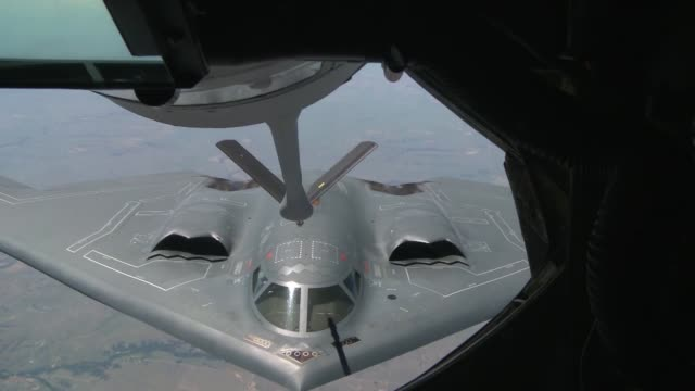 KC135 receives fuel and also gives fuel to a B2 midflight
