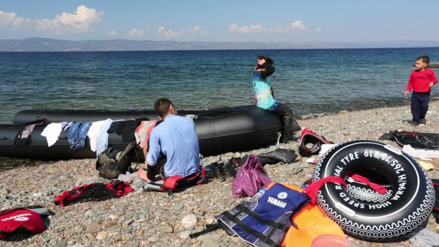 recently landed syrian migrants and boat on the greek island of lesvos. - isil konflikt stock-videos und b-roll-filmmaterial