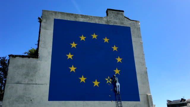 a recently painted mural by british graffiti artist banksy depicting a workman chipping away at one of the stars on a european union themed flag is... - dover kent stock-videos und b-roll-filmmaterial