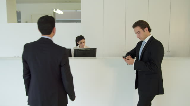 WS reception area in modern office; receptionist working, businessman standing at reception counter checking his smartphone; second businessman enters, receptionist makes phone call and directs him to his appointment; he leaves frame