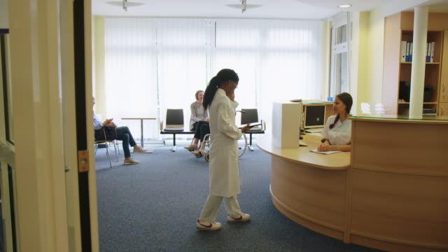 ロビーで医師に報告する受付係 - 依存点の映像素材/bロール
