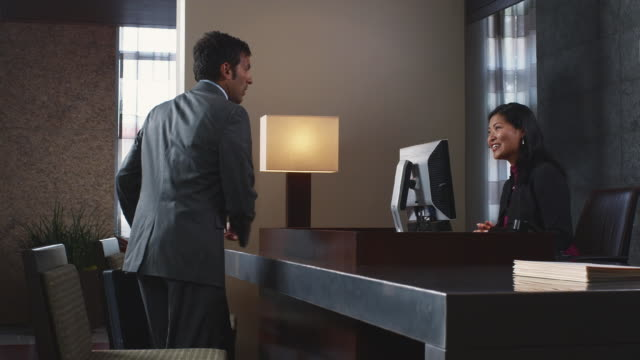 MS Receptionist greeting businessman in lobby / Bellevue, Washington, USA