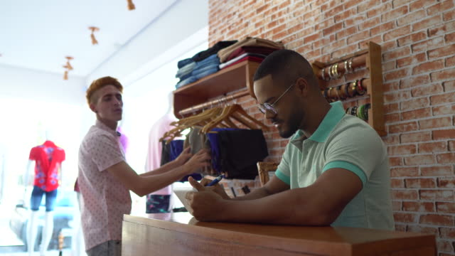 receptionist helping customer in clothing store - mesquita stock videos & royalty-free footage