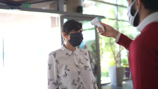 receptionist measuring temperature of employee at office's entrance - with face mask - distant stock videos & royalty-free footage
