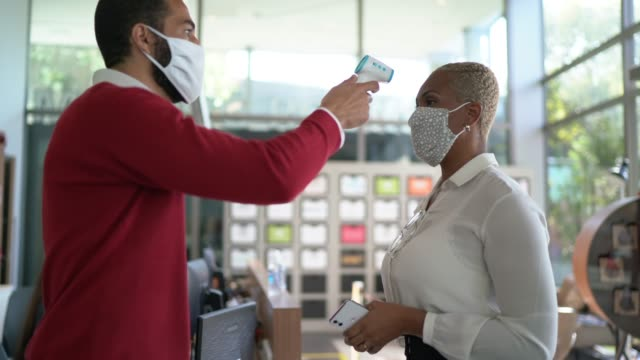 receptionist measuring temperature of female employee at office's entrance - with face mask - thermometer stock videos & royalty-free footage