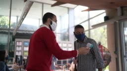 Receptionist measuring temperature of young man employee at office's entrance - with face mask