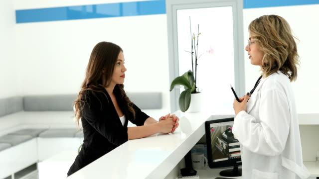 vídeos de stock, filmes e b-roll de recepcionista de clínica conversando com paciente - secretária