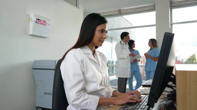 receptionist working on the front desk of a hospital - clinica medica video stock e b–roll
