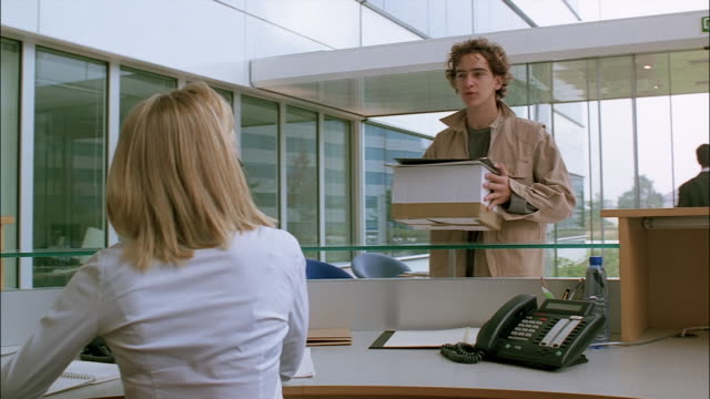 a receptionist works in an office lobby helping customers. - bürorezeption stock-videos und b-roll-filmmaterial