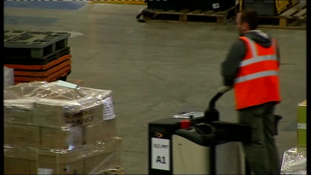 british economy shrinks 0.5%; warehouse full of amazon stock, boxes of books being moved, stock checked by workers and crates of stock along through... - warehouse点の映像素材/bロール