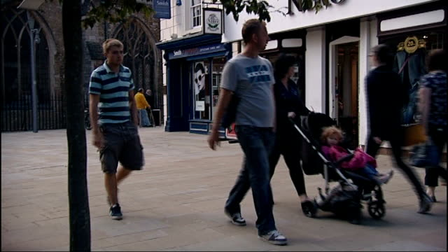 vídeos de stock e filmes b-roll de great north road reports peterborough people walking past 'shop to let' sign with pillars in foreground low angle view of people along shopping... - baixar