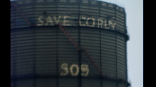 "steel firm corus cuts 3,500 jobs; tx 12.7.1979 england: northamptonshire: corby: steel works water tower with slogan ""save corby sos"" office building... - cut video transition stock videos & royalty-free footage"