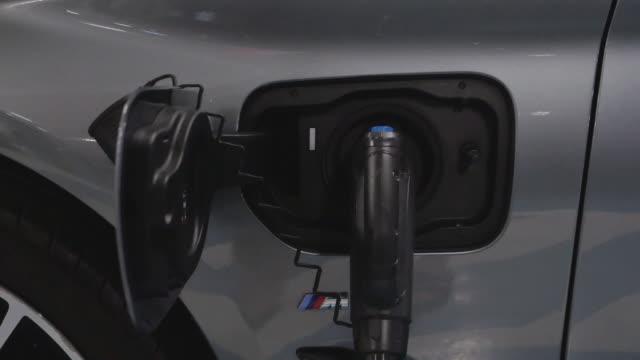 vídeos y material grabado en eventos de stock de recarga de la batería al coche eléctrico en la estación eléctrica en el aparcamiento de los grandes almacenes. vehículo eléctrico, concepto de energía renovable. - coche eléctrico coche alternativo