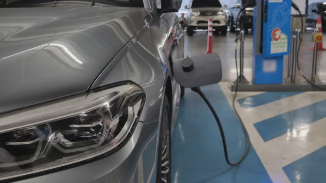 recharging battery to electric car at electric station in department store car park.electric vehicle,renewable power concept. - electric vehicle stock videos & royalty-free footage