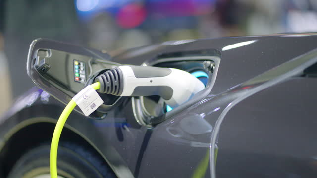 vídeos y material grabado en eventos de stock de recarga de batería a coche eléctrico en la estación eléctrica en el aparcamiento de los grandes almacenes. vehículo eléctrico, concepto de energía renovable. - coche eléctrico coche alternativo